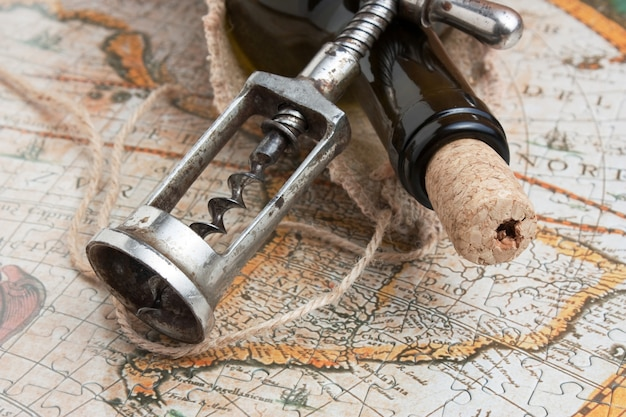 Bottiglia di vino e un cavatappi sullo sfondo di vecchie mappe