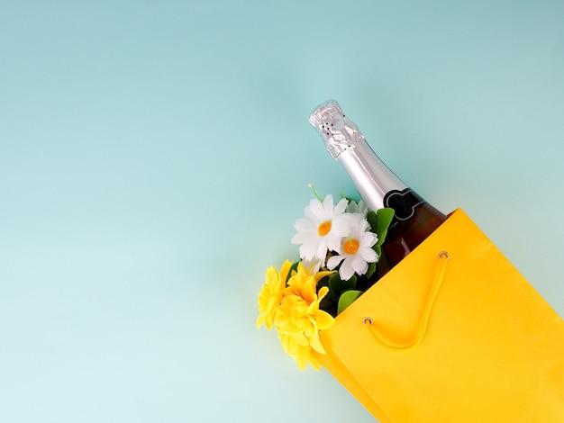 Bottiglia di vino e fiori nel pacchetto su sfondo blu