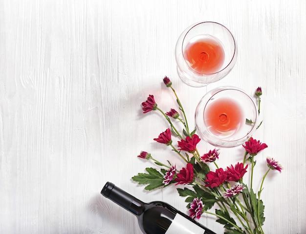 Bottiglia di vino, bicchieri e fiori su uno sfondo di legno