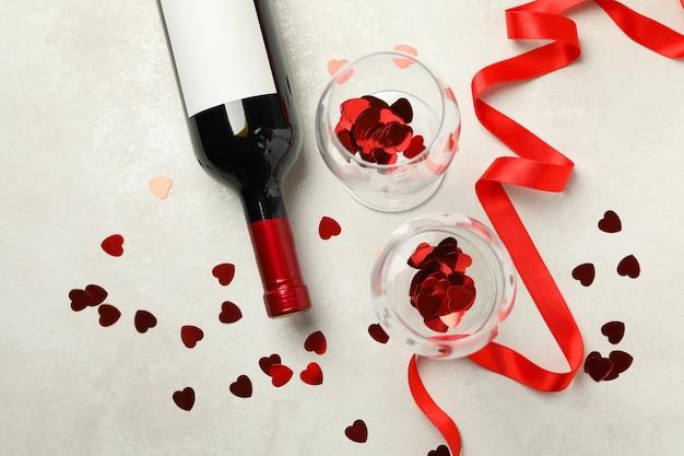 Bottiglia di vino e bicchieri con glitter e nastro sulla tabella strutturata bianca