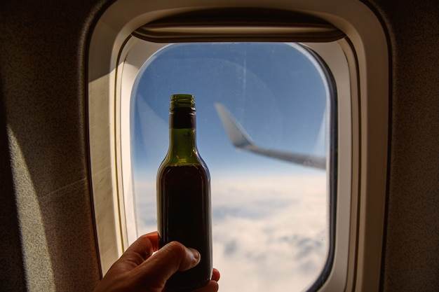 Bottiglia di vino di fronte all'oblò. alcol a bordo di un aereo.