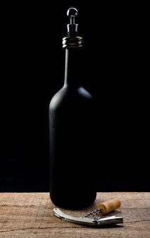 Bottiglia di vino su un tavolo in legno rustico con un cavatappi e un tappo di sughero e la bottiglia ha un tappo di vino.