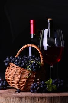 Bottiglia di vino, vino in vetro e cesto con uva