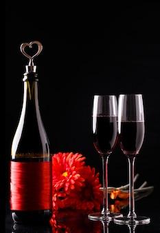 Bottiglia di vino con un tappo a forma di cuore e due bicchieri di tre gerbera rossa.