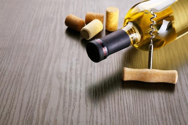 Bottiglia di vino con tappi e cavatappi sulla tavola di legno