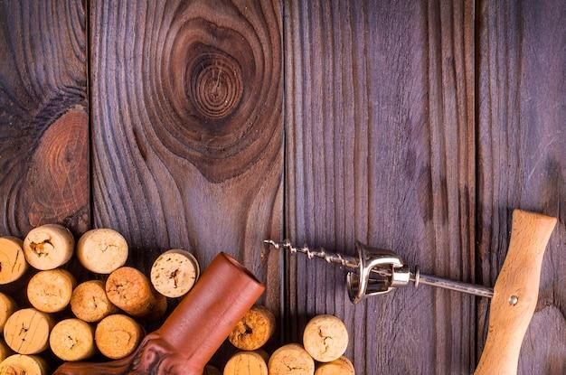 La bottiglia di vino con tappi di sughero sul fondo della tavola in legno.