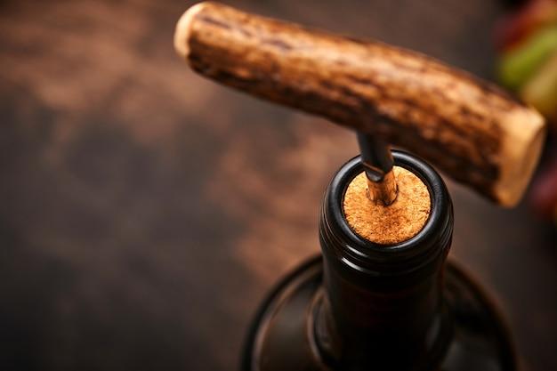 Bottiglia di vino con cavatappi. aprire una bottiglia di vino con un cavatappi in un ristorante. composizione del vino su fondo rustico scuro con lo spazio della copia. modello.