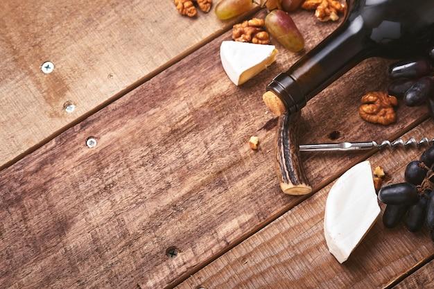 Bottiglia di vino con cavatappi. con uva, fetta di formaggio camembert, dado su sfondo grigio vecchio tavolo in cemento con spazio di copia. vino rosso con un tralcio di vite. composizione del vino su fondo rustico. modello.