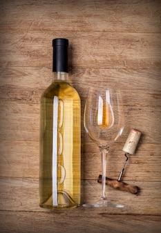 Bottiglia di vino con vetro e cavatappi su legno
