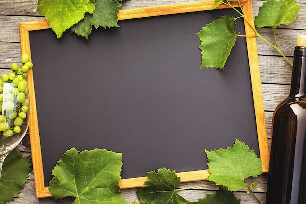 Bottiglia di vino con un bicchiere e uva su un tavolo di legno con spazio di copia