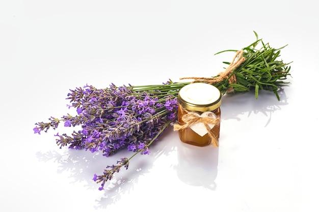 Bottiglia con olio aromatico e fiori di lavanda isolati su sfondo bianco
