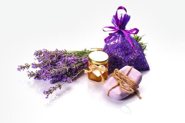 Bottiglia con olio aromatico e fiori di lavanda su bianco