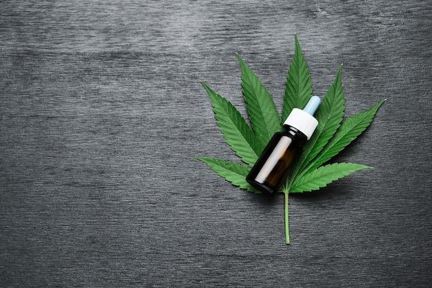 Una bottiglia con cannabis cbd o olio di canapa sulla foglia di marijuana su fondo di legno nero con spazio di copia. concetto di medicina alternativa. cosmetici e prodotti per la cura della pelle.