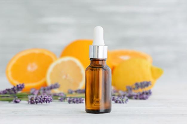 Bottiglia con olio essenziale di agrumi naturali di arancia, limone e lavanda su legno