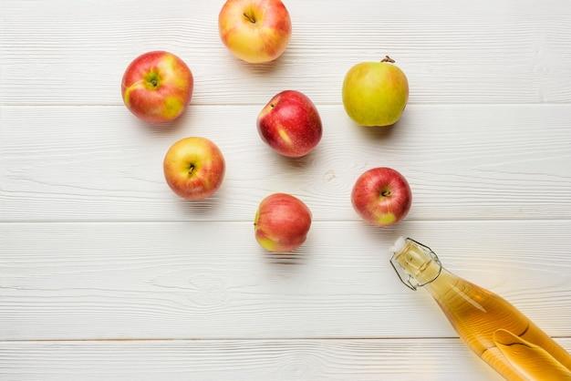 Bottiglia con sidro fatto in casa e mele su un piatto bianco con copia spazio. composizione piatta con succo di mela e mele.