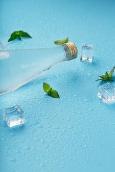 Bottiglia con una bevanda ghiacciata, cubetti di ghiaccio, gocce