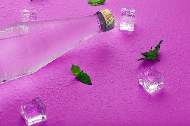 Bottiglia con una bevanda ghiacciata in gocce di condensa, cubetti di ghiaccio e foglie di menta