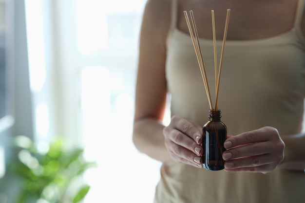 Bottiglia con bastoncini di incenso in mani femminili. medicina orientale e concetto di rilassamento
