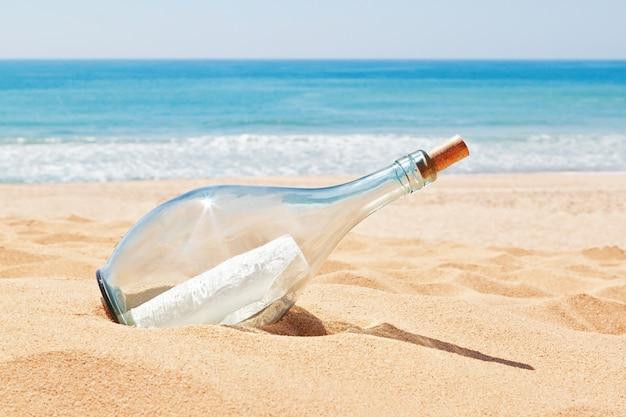 Una bottiglia con una lettera di angoscia sulla spiaggia. estate.
