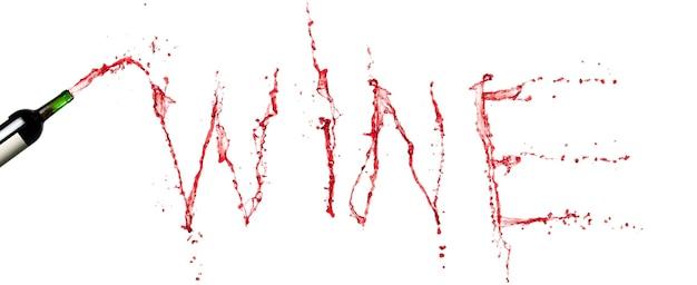 Bottiglia con spruzzi di vino rosso. parola di vino