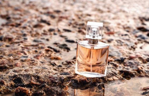 Bottiglia di profumo da donna in riva al mare su pietre con gocce d'acqua e riflessione. profumo di sole estivo di mare