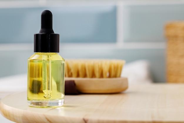 Bottiglia di olio cosmetico giallo sulla fine del vassoio di legno sulla foto
