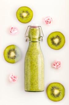 Frullato di kiwi in bottiglia con fette di kiwi fresco e fiorellini in un bagno di latte. bevanda vegetariana, biologica, bio e detox. concetti di nutrizione, dietetica, assistenza sanitaria, benessere e stile di vita.