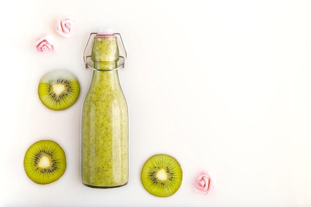 Frullato di kiwi in bottiglia con fette di kiwi fresco in un bagno di latte. bevanda vegetariana, biologica, bio e detox. concetti di nutrizione, dietetica, assistenza sanitaria, benessere e stile di vita. spazio per il testo.