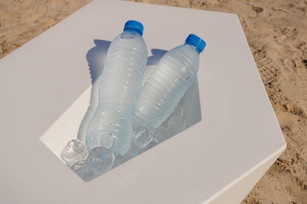 Acqua in bottiglia su cubetti di ghiaccio in una calda giornata sulla spiaggia di sabbia. concetto di problema di plastica ed ecologia.