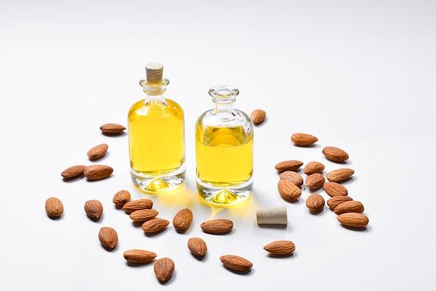 Bottiglie di olio di mandorle e mandorle su sfondo bianco