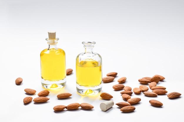 Bottiglie di olio di mandorle e mandorle su bianco