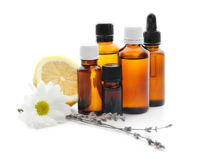 Bottiglie di olio essenziale di agrumi, limone e fiori su superficie bianca