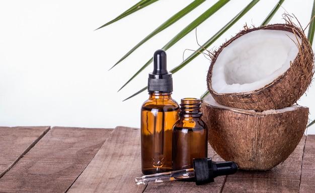 Bottiglie di oli aromatici di cocco su un tavolo di legno con una copia dello spazio.