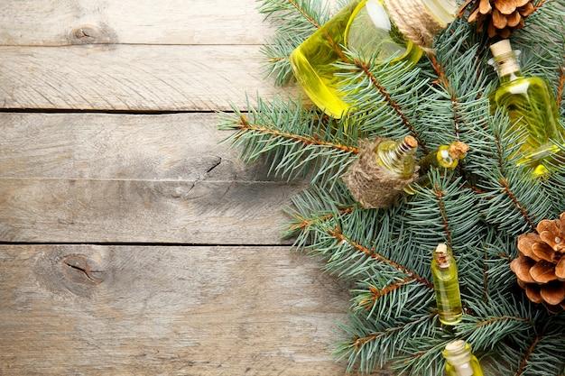 Bottiglie di olio essenziale di conifere, rami e strobili su fondo di legno