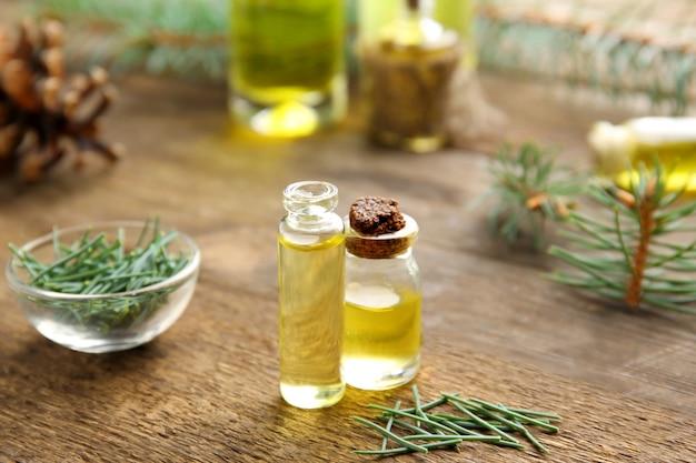 Bottiglie di olio essenziale di conifere e ciotola di vetro su fondo di legno, vista ravvicinata