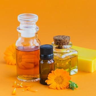 Bottiglie di olio cosmetico, aromatico o essenziale e fiori freschi di calendula sull'arancia