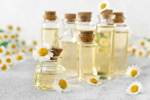 Bottiglie di olio essenziale con fiori di camomilla sul tavolo grigio