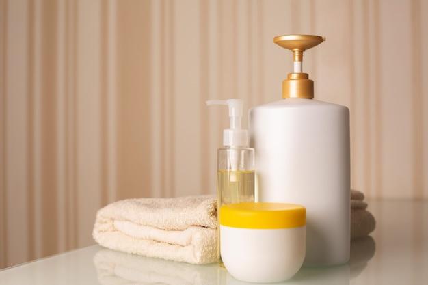 Bottiglie di shampoo per capelli, olio detergente e burro per il corpo con asciugamano da bagno su una scrivania su uno sfondo beige neutro. spazio per il testo