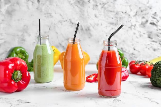 Bottiglie di frullato sano con diverse verdure su superficie chiara