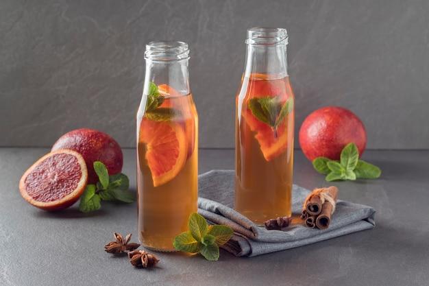 Bottiglie di kombucha con arance insanguinate sul tavolo grigio