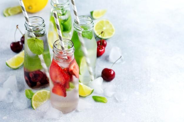 Bottiglie di limonata rinfrescante limonata estiva con lime, fragola, ciliegia, cetriolo e ghiaccio su una superficie di cemento grigio.