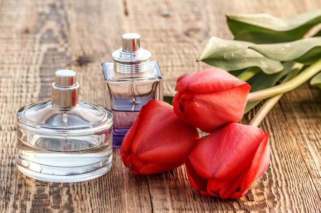 Bottiglie di profumo su tavole di legno con tulipani rossi.