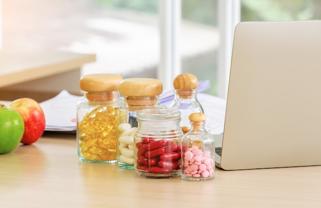 Bottiglie di pillole, capsule e vitamine con computer portatile e frutta fresca sulla scrivania del nutrizionista