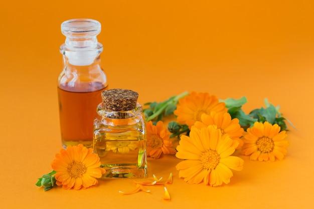 Bottiglie di tintura o infuso di calendula e olio essenziale con fiori freschi di calendula su arancia