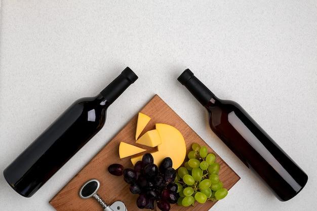 Bottiglie di vino rosso e bianco su sfondo bianco dalla vista dall'alto