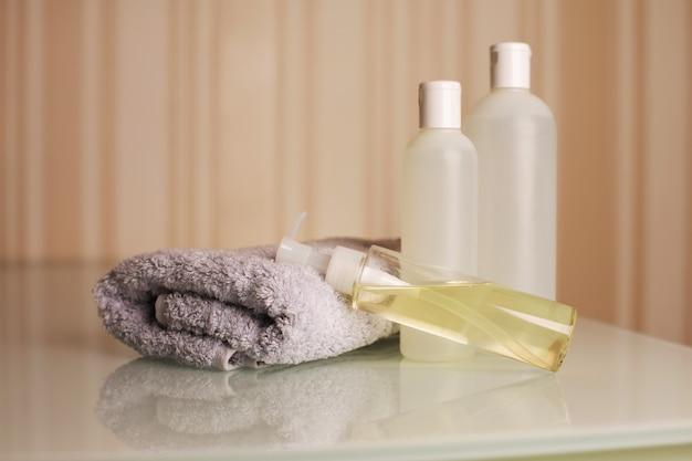 Bottiglie di shampoo, bagnoschiuma e olio micellare con asciugamano su una scrivania su uno sfondo beige neutro. spazio vuoto