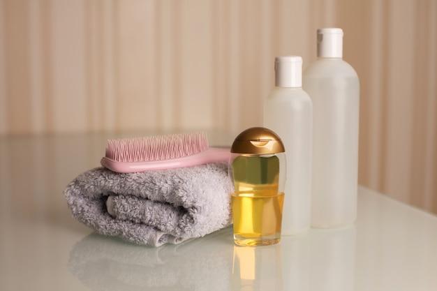 Bottiglie di shampoo, pettine e gel doccia con asciugamano da bagno su una scrivania su uno sfondo beige neutro. spazio per il testo