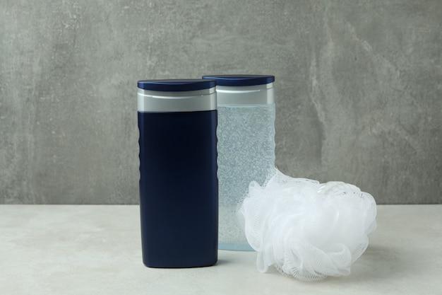 Bottiglie di gel doccia e salvietta contro uno sfondo grigio