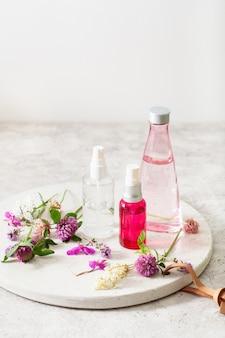 Bottiglie lozione per la cura della pelle siero fiori medicinali erbe. cosmetico naturale. trifoglio millefoglie tanaceto rosebay
