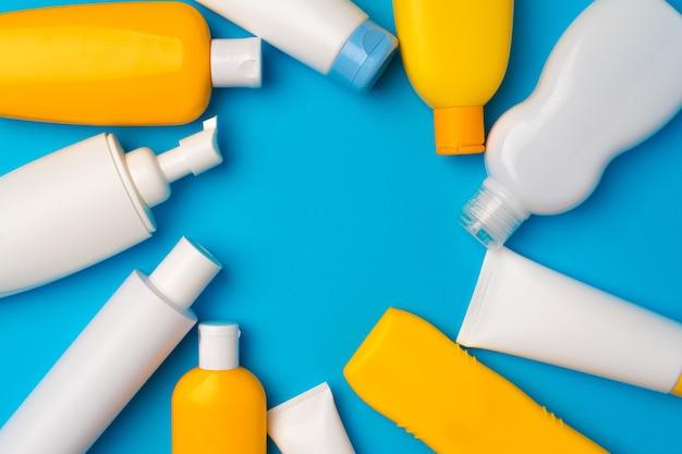 Bottiglie di crema solare su sfondo blu